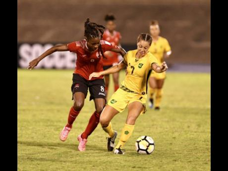 Trinidad and Tobago's Patrice Superville challenges Jamaica's Chinyelu Asher (right) during a Concacaf Women's Championship game at the National Stadium on Friday, August 31, 2018.