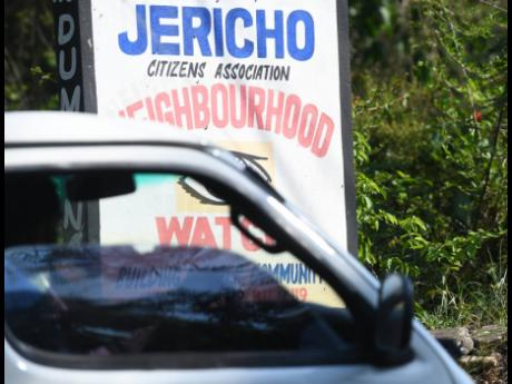 A motorist drives by a sign in the community of Jericho, just outside Linstead, in St Catherine yesterday.