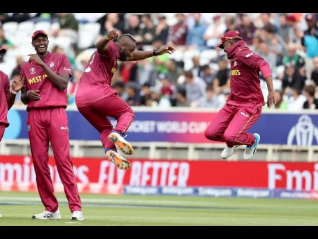 Windies' bowler Andre Russell (centre) celebrates with Darren Bravo (right) after taking the wicket of Pakistan's Haris Sohail as captain Jason Holder looks on during a Cricket World Cup match at Trent Bridge cricket ground in Nottingham, England on Friday, May 31, 2019.