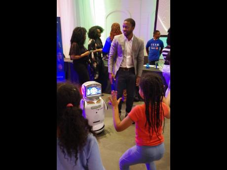 School age child tests the capabilities of GlobalDWS'sTeacher's Assistant robot. The first of it'skind in the world. Standing beside robot: Dwayne Matthews, education consultant, GlobalDWS.