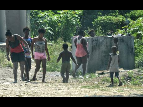 Residents of Majesty Gardens, St Andrew, bathe at a standpipe shortly before the 3 p.m. curfew deadline on Good Friday. They have complained of the indignity of showering outside and not having access to enclosures nearby.