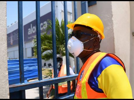 Portmore Mayor Leon Thomas standing at the entrance to Alorica facility where two workers recently tested positive for the coronavirus.
