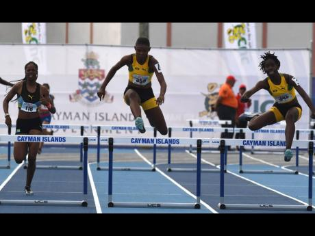 Jamaica's Sashell Reid (centre) and Quaycian Davis (right) storm by the Bahamas' Reshae Dean on their way to gold and silver, respectively, in the Girls Under 17 400m hurdles final at the Carifta Games, in the Cayman Islands on Sunday, April 21, 2019.