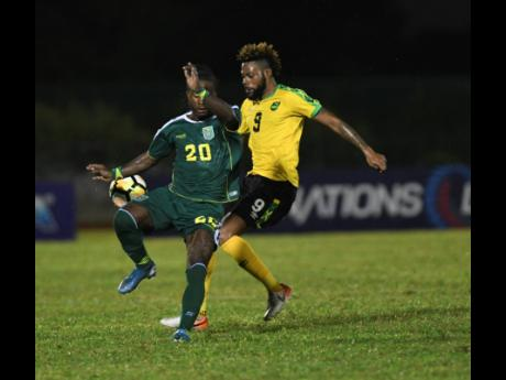 Jamaica's Ricardo Morris (right) gets up close with Guyana's Trayon Bobb to make a challenge during their Concacaf Nations League match at the Montego Bay Sports Complex on Monday, October 18, 2019. Social-distancing protocol requires persons to stay at least three feet away from each other to help curtail the transmission of COVID-19, posing questions for the resumption of contact sports such as football.