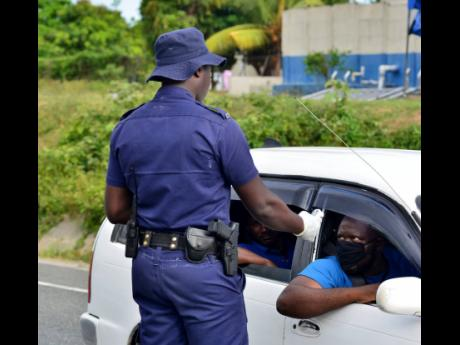 A policeman conducts a temperature check on a motorist in the vicinity of Angels, St Catherine, on Wednesday.