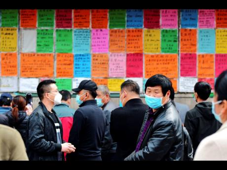 In this April 8, 2020 photo, labourers wear face masks to protect against the spread of the new coronavirus as they look at job postings at a labour market in Qingdao in eastern China's Shandong Province. China has reported its biggest economic decline since the 1970s as it fought the coronavirus in the first quarter of the year.