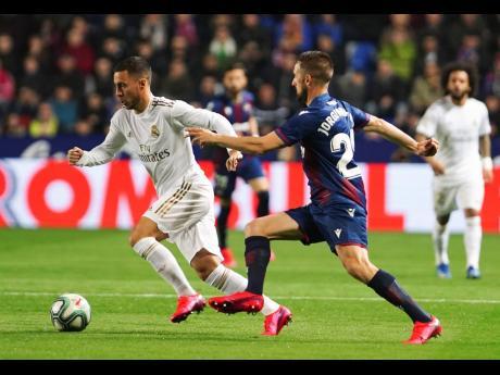 Real Madrid's Eden Hazard (left) is harried by Levante's Jorge Miramon during their La Liga match at the Ciutat de Valencia Stadium in Valencia, Spain, on Saturday, February 22.