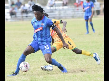 Vere's Ricardo Messam was deceived into going the wrong way by Dunbeholden captain Shaquille Dyer (front) during their Red Stripe Premier League match at the Wembley Centre of Excellence in Hayes, Clarendon, on Sunday, February 16.
