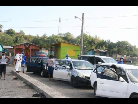 Taxis being sanitised in the Lucea Transport Centre under an initiative lauched by Hanover Strong on Sunday.