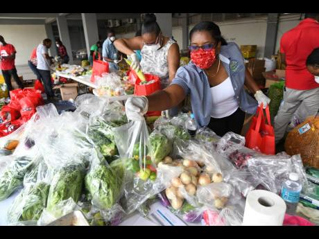 Kerri-Ann Smith (left) and Judith Leslie-Alexander package produce for the first Drive-Thru Farmers' Market hosted by the Agro-Investment Corporation at the AMC complex on Spanish Town Road on Wednesday. Rudolph Brown/Photographer