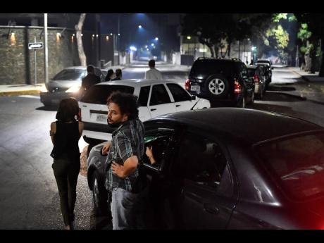 People stand close to their vehicles as they wait in line to fill up their vehicles with gasolene in Caracas, Venezuela, on Saturday, April 11.