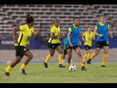 Jamaica's Christina Chang (second right) plays a pass into the path of Mireya Grey (left) during a senior women's team training session at the National Stadium in Kingston on Monday, May 13, 2019.