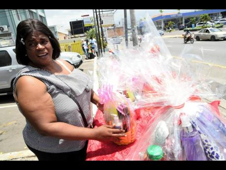 Tanya Rowe puts out Mother's Day gifts for sale on Constant Spring Road in Kingston yesterday.