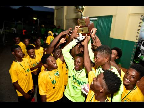 Excelsior High School footballers hoist the Ali Cup  to celebrate winning the tournament at the Courtney Walsh Oval on Saturday, July 20, 2019.