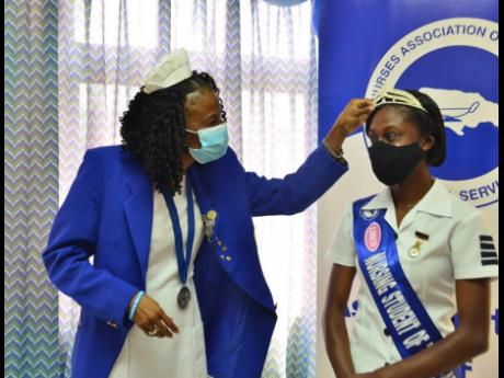 Nurses' Association of Jamaica (NAJ) President Carmen Johnson (left) fixes the crown of Student Nurse of the Year, Taquise Campbell, at the launch of National Nurses' Week Activities at the NAJ's St Andrew offices yesterday.
