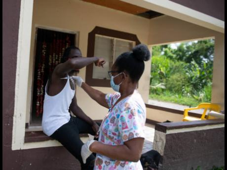 Ricardo Edwards has his temperature taken by Audrey Hinds-McLeod, one of 70 healthcare workers who went on house-to-house visits in Dover, St Mary, on Saturday, May 9.