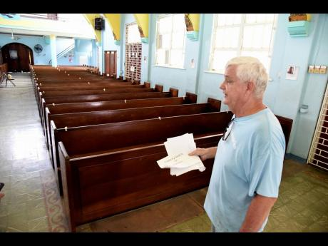 Brother Bernie Spitzley, church administrator walks by empty  benches inside the Holy Rosary Roman Catholic Church in East Kingston yesterday. He was at the church preparing for service tomorrow where some 72 members will be accommodated at any one time for service.