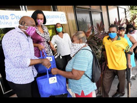 Senator Floyd Morris; his wife, Shelley-Ann (second left); and Gloria Goffe (third left), executive director of the Combined Disabilities Association of Jamaica, hand out packages and supplies to people with disabilities. Collecting her package is Lorna Pinnock while Errol Williams (second right) and Denise Wray await their turn at the Combined Disabilities offices at 18 Ripon Road on Tuesday of this week.