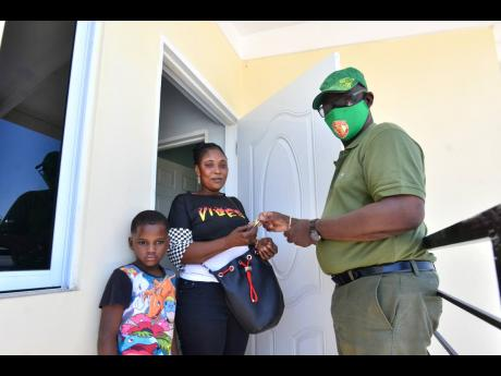 Local Government Minister Desmond McKenzie hands to Nicole Francis, seen here alongside her son, Damion Green, keys to their new home on Elgin Street, Denham Town, on Monday. Francis lost her home to fire nine years ago.