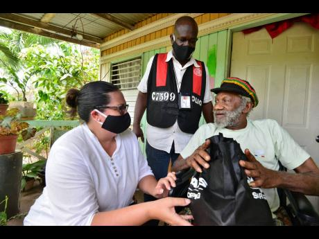 Saffrey Brown (left), chairman of the Council of Voluntary Social Services, and Deputy Superintendent Rory Martin deliver a care package to Joseph Heslop, who is unable to walk, in the community of Central Village,  St Catherine, on Saturday. The distribution drive was part of the PSOJ's COVID-19 relief programme.
