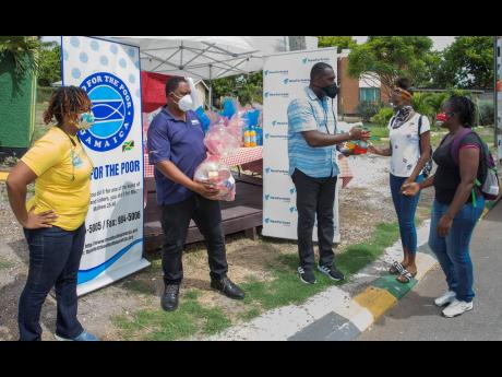Principal of Old Harbour High School, Linton Weir, is happy to hand a care package to grade-eight student Indiran Robinson and her mother, Tracey-Ann Hardware, at the school earlier this week, courtesy of New Fortress Energy (NFE) Foundation and Food For The Poor (FFP). Also in the photo (from left) are Kivett Silvera, executive director at FFP, and Joel Campbell, community liaison officer at NFE.