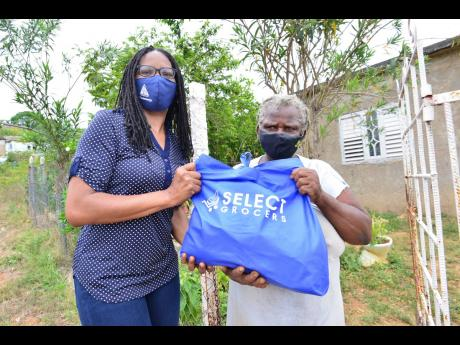 Shelly-Ann Lawson Francis (left), executive director of Council of Voluntary Social Services, delivers a care package to Carmen Heaven of Zambia, St Catherine, last Saturday as part of the PSOJ's COVID-19 food distribution programme.