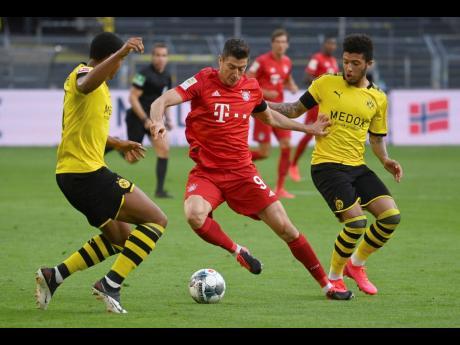 Munich's Robert Lewandowski (centre) and Dortmund's Jadon Sancho (right) challenge for the ball during the German Bundesliga match between Borussia Dortmund and FC Bayern Munich in Dortmund, Germany, yesterday. Bayern won 1-0.