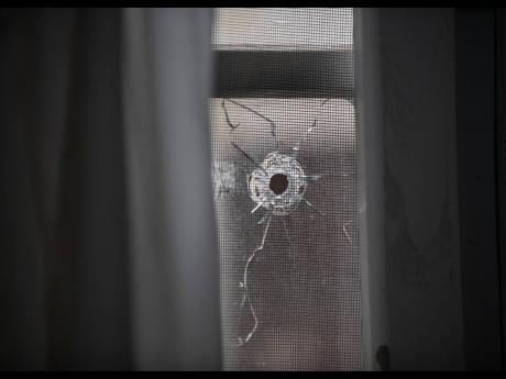 One of numerous bullet holes left at a home on Bryce Hill Road, August Town, St Andrew, yesterday.  Attackers sprayed bullets into the home the previous night injuring three of the occupants including an eight-year-old.