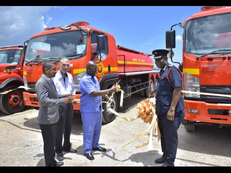 In this 2018 Gleaner photo, Minister of Local Government and Community Development Desmond McKenzie (third left) cuts the ribbon symbolising the official handover of four new fire trucks to the Jamaica Fire Brigade in Kingston. Others sharing in the moment