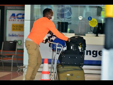 A Jamaican citizen arrives at the Norman Manley International Airport on Saturday, May 30. Effective today, Jamaicans who have been stranded overseas by coronavirus restrictions can return home on regularly scheduled flights.