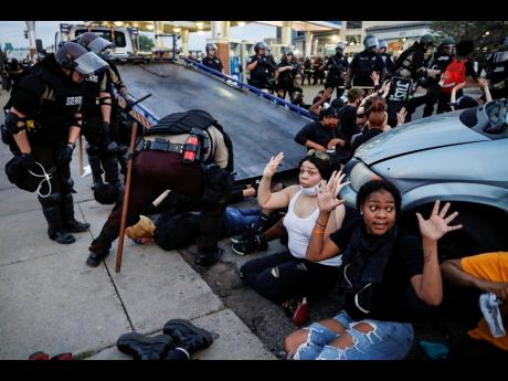 Protesters raise their hands on the command of the police as they are detained prior to arrest and processing at a gas station on South Washington Street, Minneapolis, on Sunday, May 31. The protests were sparked by the death of George Floyd, who died afte