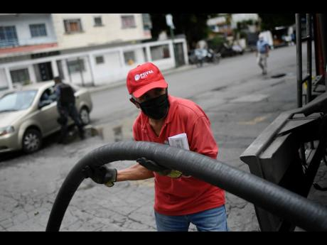 A worker wearing a face mask amid the new coronavirus pandemic fills one of the tanks of a state oil company gas station in Caracas, Venezuela, on Sunday, May 31.