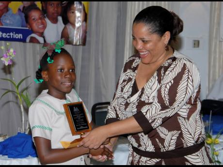 Eight-year old Lori-Ann Mullings of Excelsior Primary School receives an award from Alison McLean, then CEO of the Child Development Agency, at the National Child Month Committee 2007 Community Service Awards ceremony at the Alhambra Inn in Kingston.