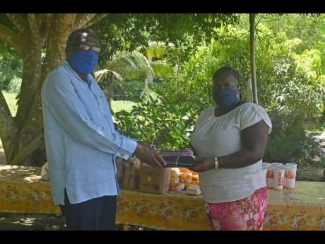 St James Custos Bishop Conrad Pitkin presents a gift of 100 face masks toCordell Howell-Huie, the administrator of the Mustard Seed Children's Home in Adelphi, St James. Forty-eight lunches from Burger King were also bought for the home's children, c