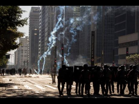 AP  Police clash with anti-government demonstrators in São Paulo, Brazil, on Sunday, May 31. Police used tear gas to disperse anti-government protesters in Brazil's largest city as they began to clash with small groups loyal to President Jair Bolsonaro.