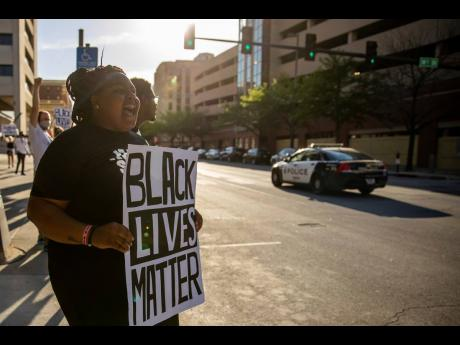 Sydnee Harris of Omaha, Nebraska, joins dozens of others staging a rally, holding a Black Lives Matter poster outside the Omaha Douglas Civic Center in Omaha on Wednesday.