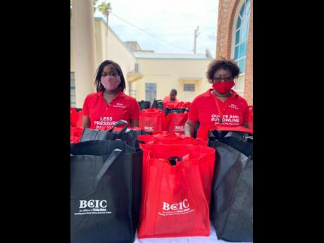 Sponsorship and Public Relations Executive Davee Williamson (left) and Human Resource Manager Doreen Samuels prepare to handover care packages to persons at the Scots Kirk United Church on Duke Street on May 23.