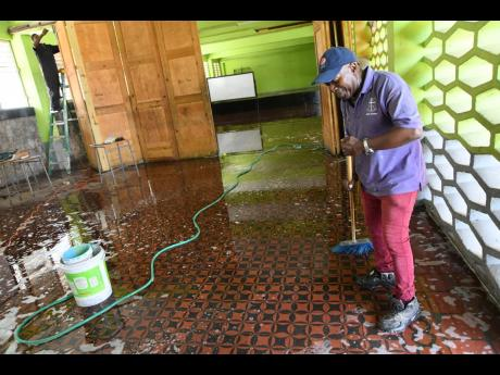 Maintenance staff at Kingston Technical High School cleaning the floors to prepare for the reopening of school. Health officials in western Jamaica have voiced concerns about the prepardeness of the schools in their region as they reopen today, Monday, Jun