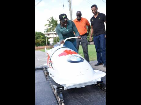 National female bobsledder Carrie Russell (left) shows off her sled to Sports Development Foundation General Manager Denzil Wilks and Jamaica Bobsled and Skeleton Federation President Nelson Stokes during a training session at the GC Foster College of Phys