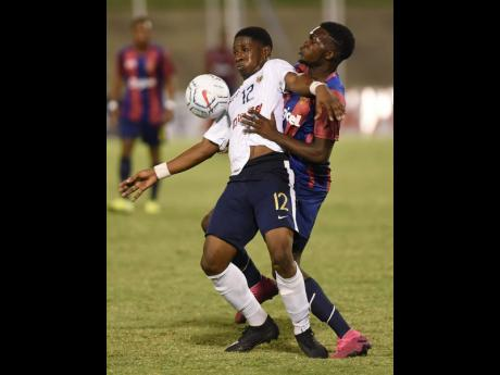 Richard Thompson (left) from Jamaica College (JC) holds off a challenge from Kaman Davis from St Andrew Technical during the 2019 ISSA Manning Cup football final. JC won 5-4 on penalties to win the title.