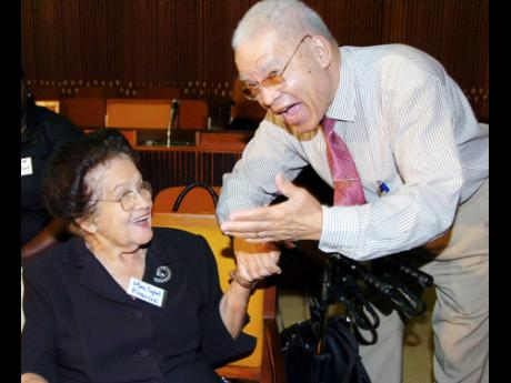 Sybil Francis (left), former director of the Social Welfare Training Centre and chairman of the National Council for Senior Citizens, shares a light moment with Clinton Davis, president of the Jamaica Government Pensioners' Association, at the disclosure