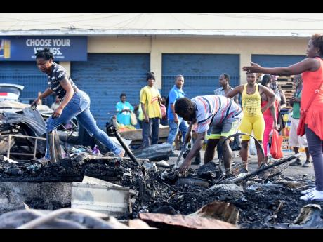 Distraught vendors sift through charred rubble yesterday after fire destroyed the Rae Rae Market in downtown Kingston overnight.
