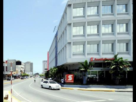 A car drives by a Scotiabank branch in New Kingston.