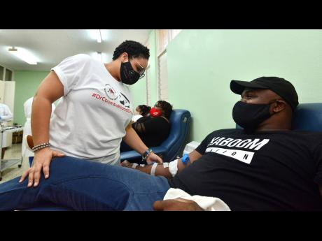 Dr Danielle Levy (left), medical officer at the National Blood Transfusion Service, checks on blood donor Jabari Wallace during a blood drive organised by Dr Phillip Coombs last month.