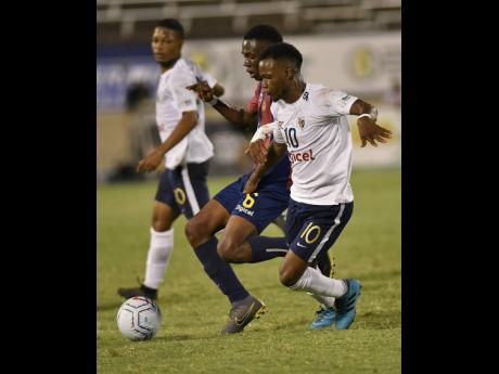 Jamaica College's Omar Thompson (right) challenges St Andrew Technical High School's Mikel Riley for ball possession during the ISSA/Digicel Manning Cup final at the National Stadium on Friday, November 29, 2019.
