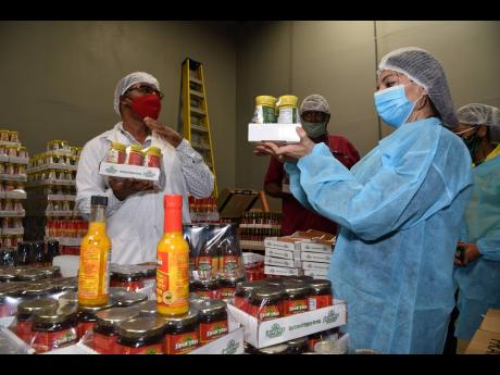 Albert Bailey (left), CEO, Spur Tree Spices, shows off a range of products that the company produces to Guillen Grillo (right), Costa Rican chargé d'affaires to Jamaica, during a tour of the factory yesterday. Mohan Jagnarine (centre) executive director