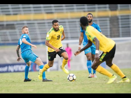 Jamaica's Adrian Mariappa (second left) dribbles away from Aruba's midfielder Erik Santos (left) and Terence Groothusen (obscured) during a Concacaf Nations League game at the National Stadium on Saturday, October 12, 2019.