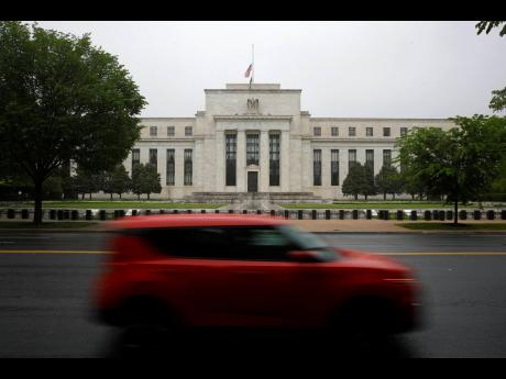 In this May 22, 2020 photo, a car drives past the Federal Reserve building in Washington.