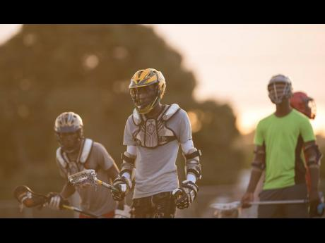 Nathanel Moulton (centre) and other members of Jamaica College's lacrosse team go through a training session at the Jamaica College Ashenheim Stadium on January 16, 2020.