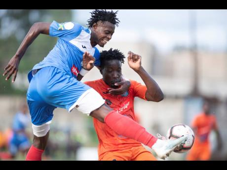Chavany Willis (left) of Portmore United takes a shot at goal while under pressure from Tivoli Gardens FC's Jabeur Johnson during a Red Stripe Premier League match at the Spanish Town Prison Oval earlier this year.